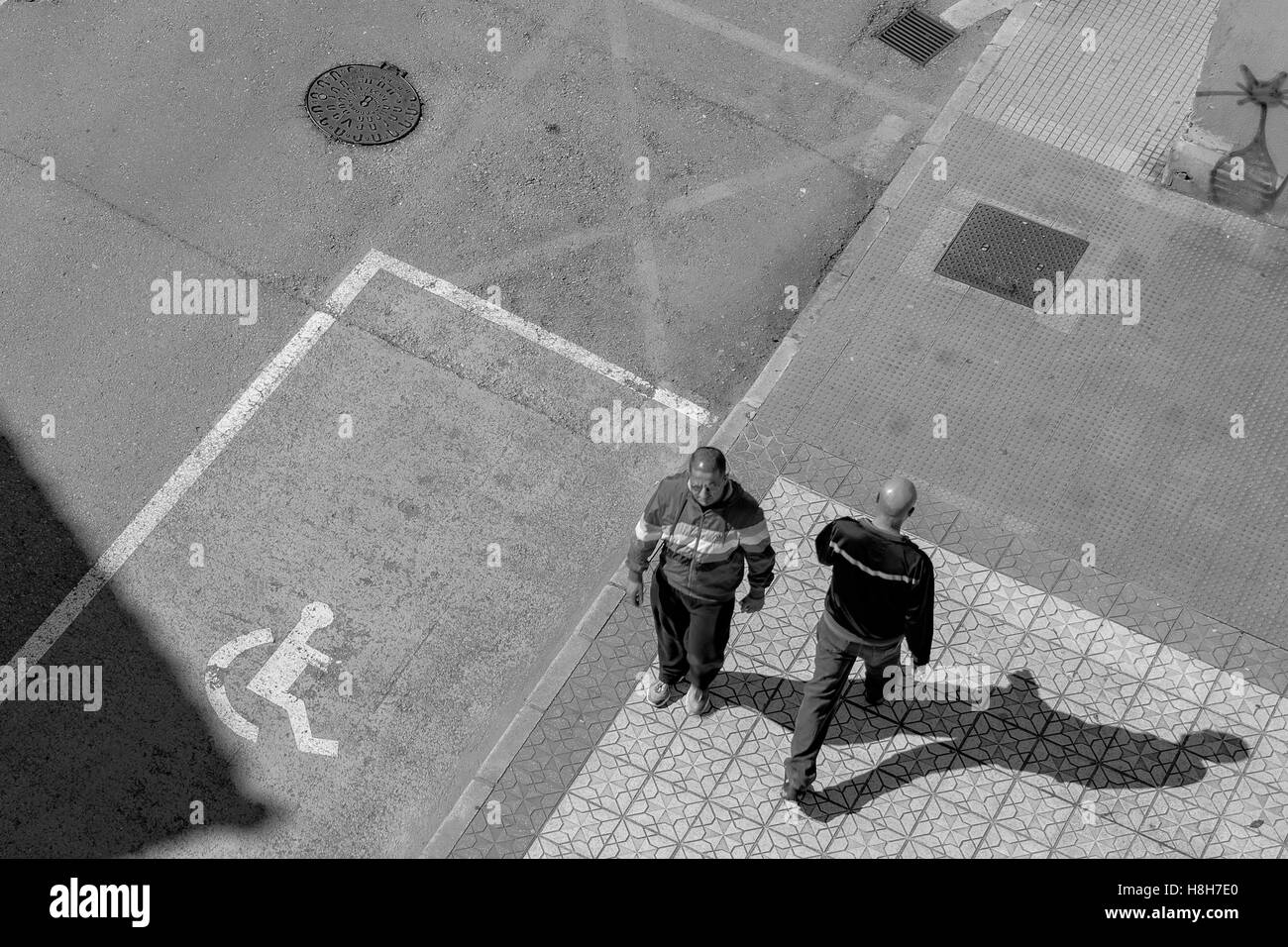 Two men crossing in the street of the town of Colincres, Cantabria, Spain, Europe. - Stock Image