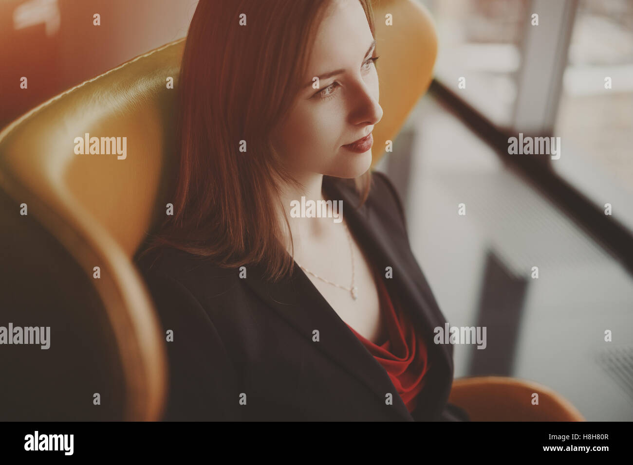 Portrait of young successful woman entrepreneur in a red dress and jacket sitting on orange armchair near window - Stock Image