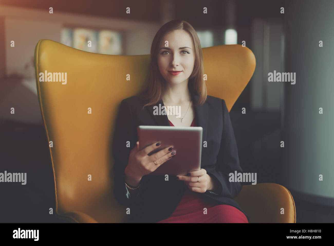 Portrait of young successful woman entrepreneur in a red dress and jacket sitting on orange armchair and working - Stock Image