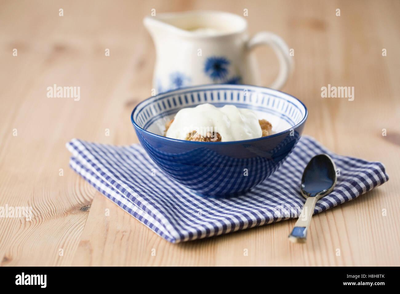 Apple crumble and vanilla custard. - Stock Image