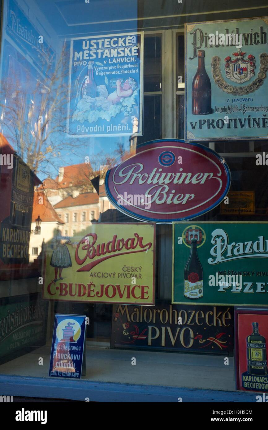 Assortment of beer advertisements in a shop window, Cesky Krumlov - Stock Image