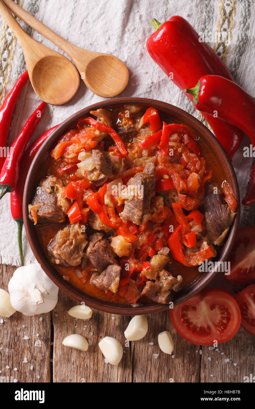 lamb slow stewed with onion, tomato and pepper close-up in a bowl on the table. vertical view from above - Stock Image