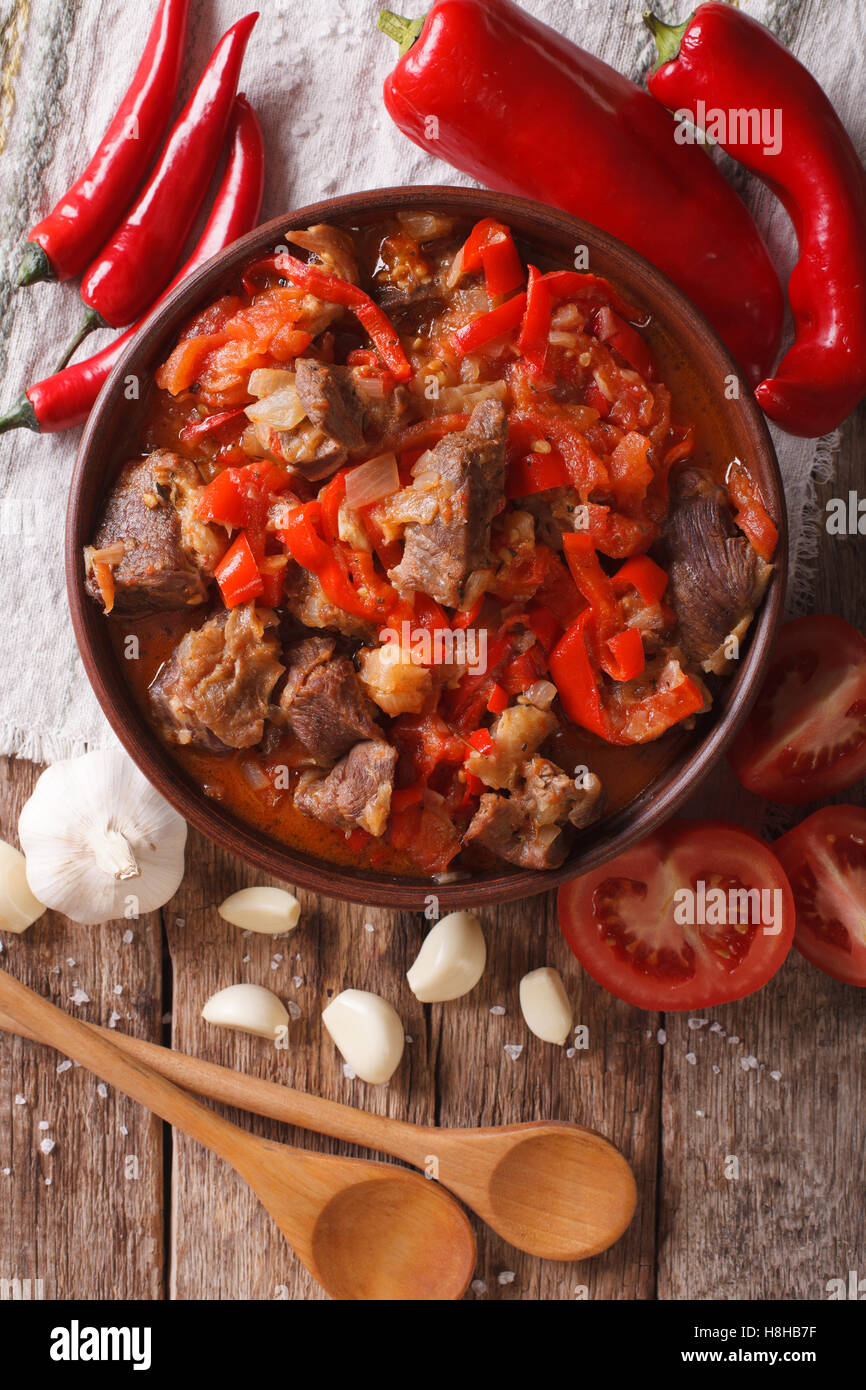 pieces of lamb cooked with onion, tomato and pepper close-up in a bowl on the table. vertical view from above - Stock Image