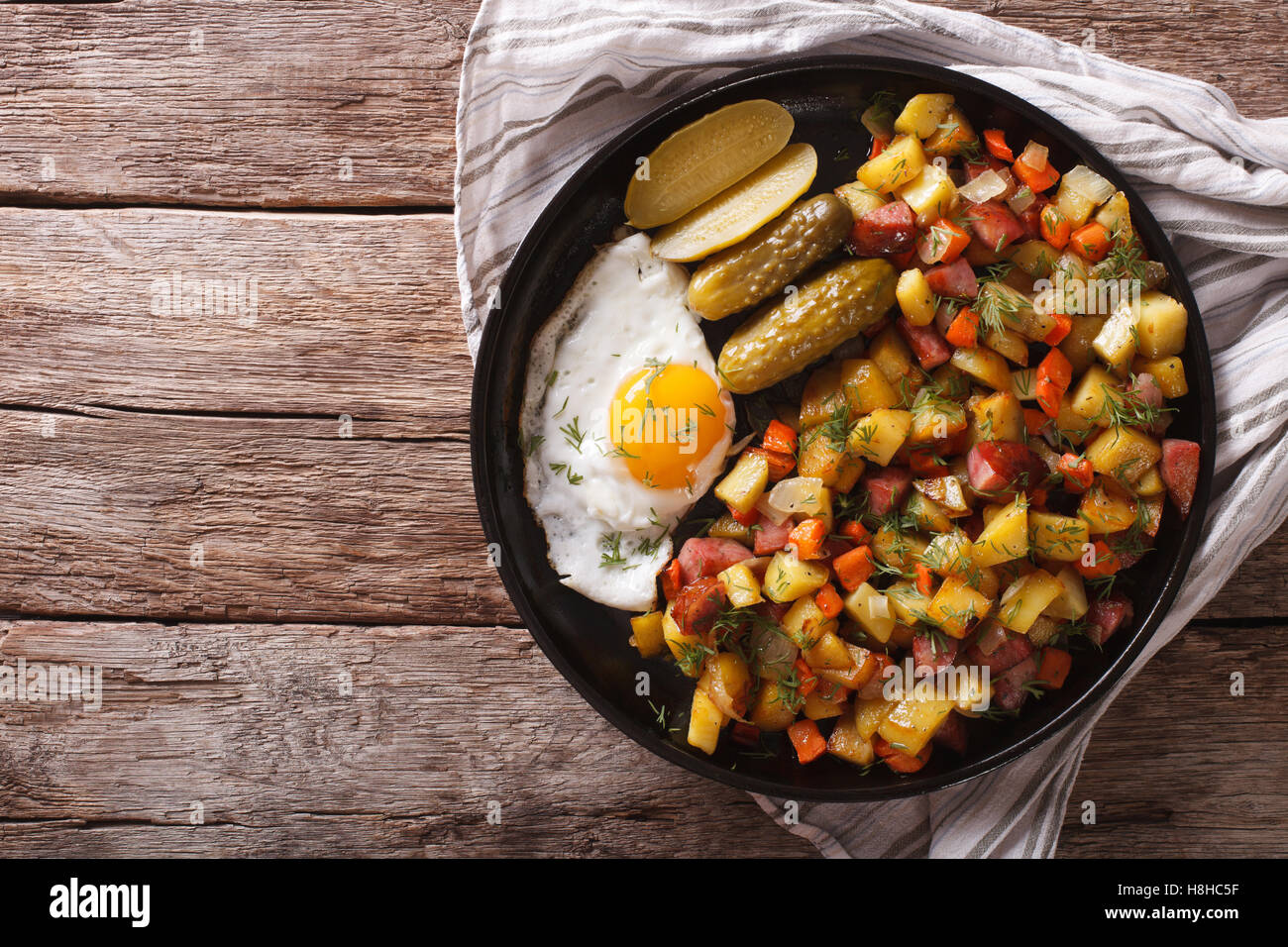 Finnish food pyttipannu: fried potatoes with sausages, eggs and pickled cucumbers close-up on a plate. Horizontal - Stock Image