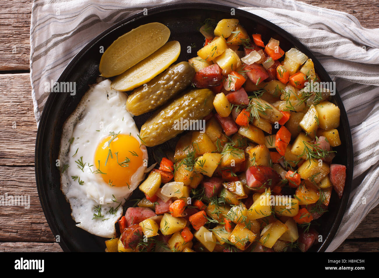 Norwegian food pyttipanne: fried potatoes with sausages, eggs and pickled cucumbers close-up on a plate. Horizontal - Stock Image