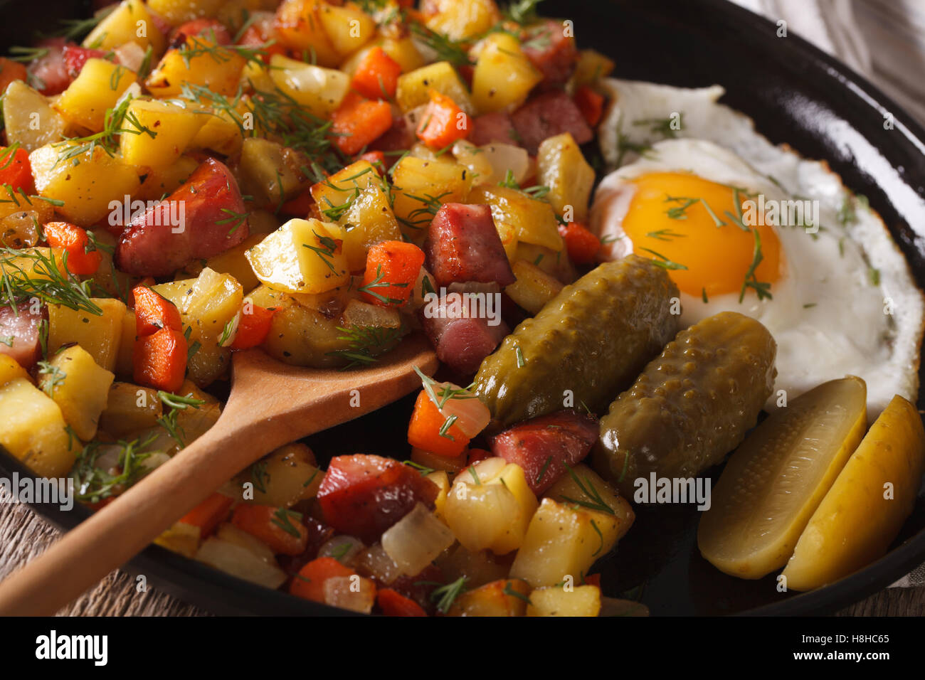 Scandinavian breakfast: pyttipanna with fried eggs and pickled cucumbers close-up on a plate. horizontal - Stock Image
