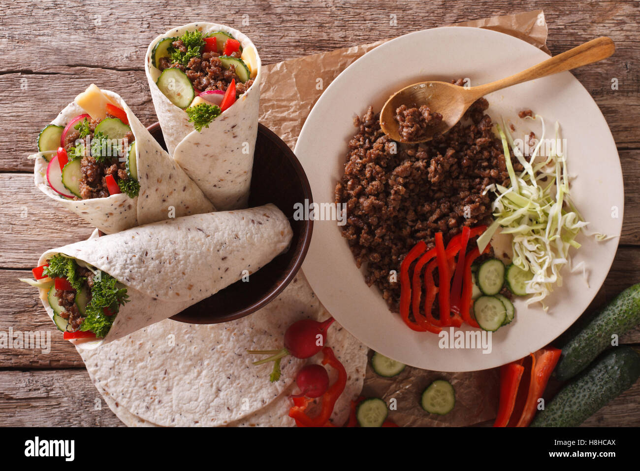Sandwich roll stuffed with beef and vegetables close-up on the table. horizontal view from above - Stock Image