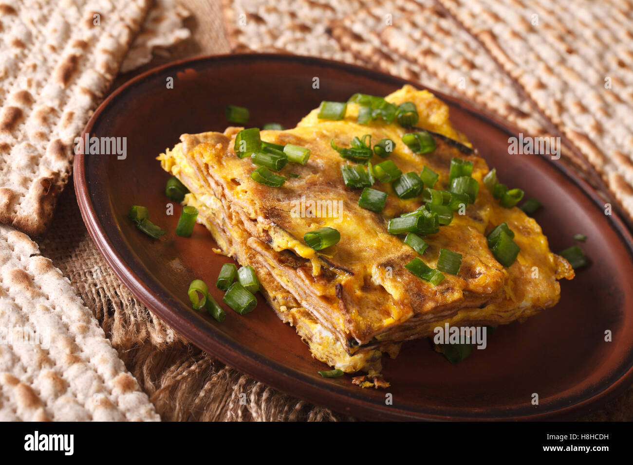 Jewish cuisine: matzah brei with green onions close-up on a plate. horizontal - Stock Image