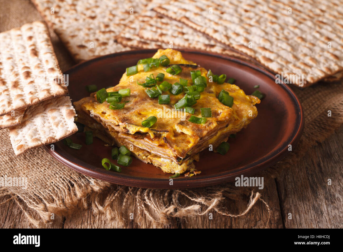 Jewish omelette: matzah brei with green onions close-up on a plate. horizontal - Stock Image