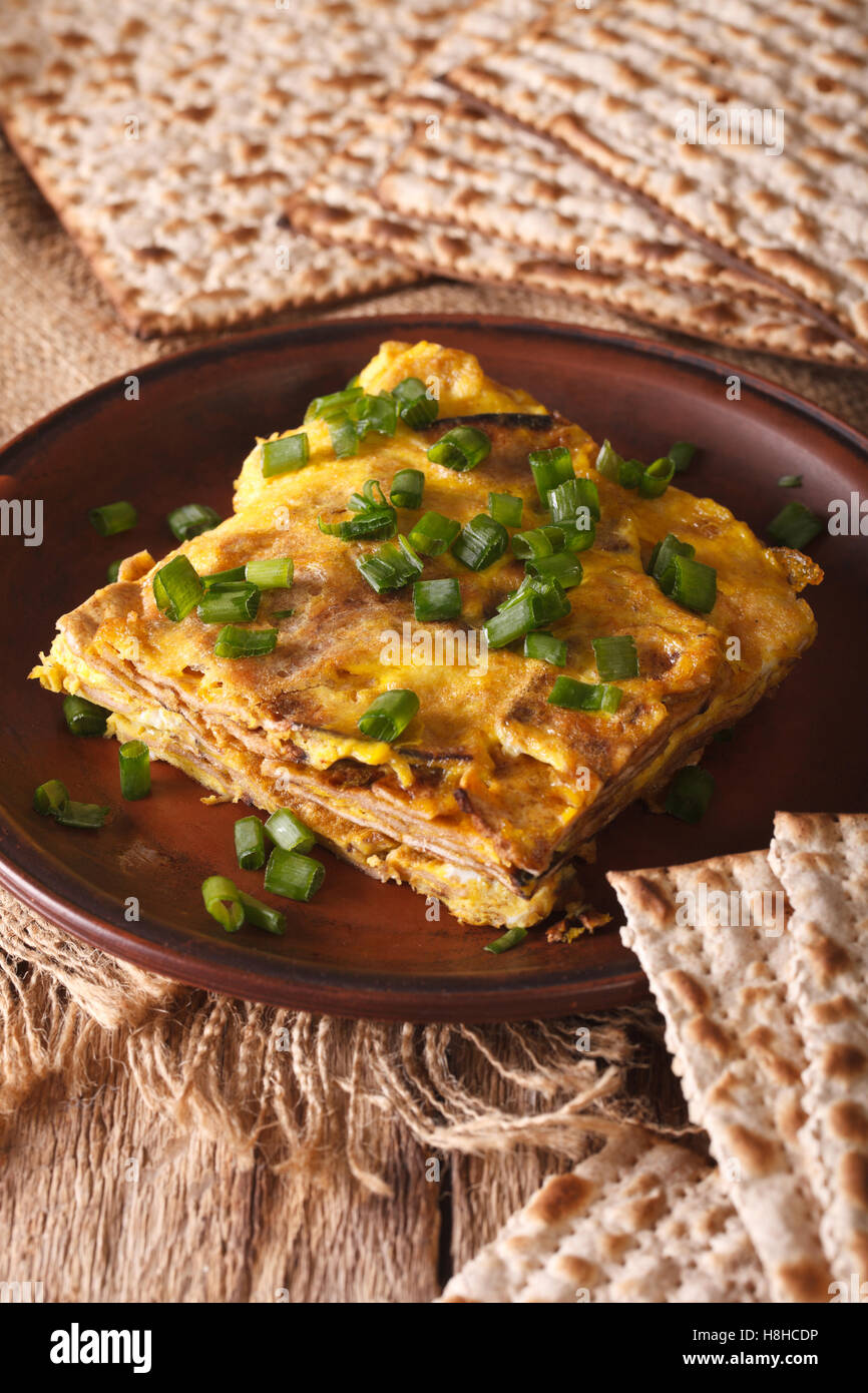 Jewish cuisine: matzah brei with green onions close-up on a plate. Vertical - Stock Image