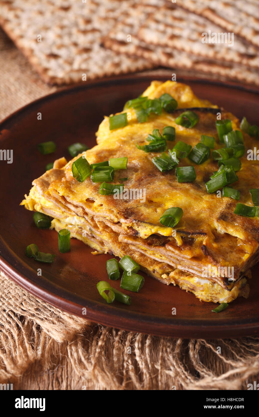Matzo fried with eggs and green onions - matzah brei close-up on a plate. vertical - Stock Image