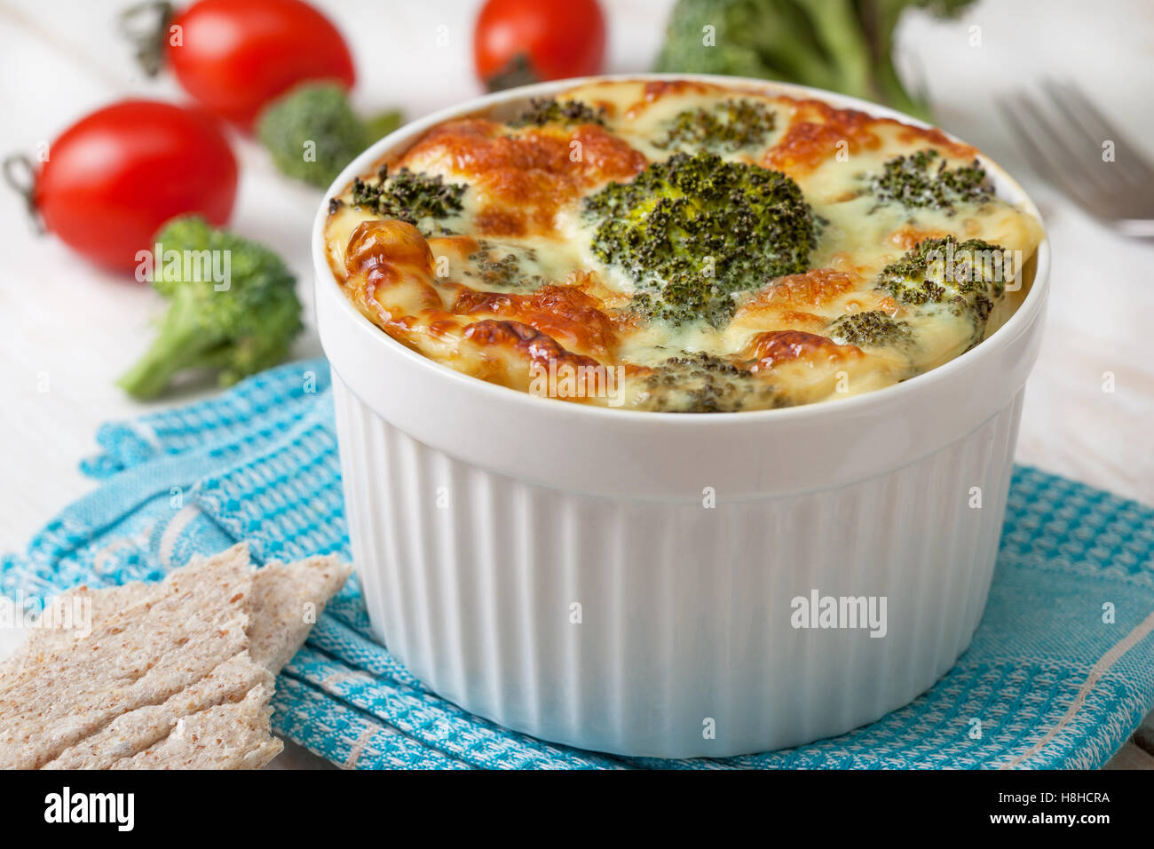 Healthy dietary breakfast. Broccoli casserole with eggs, cheese in a white bowl, fresh tomatoes, crisp bread on - Stock Image