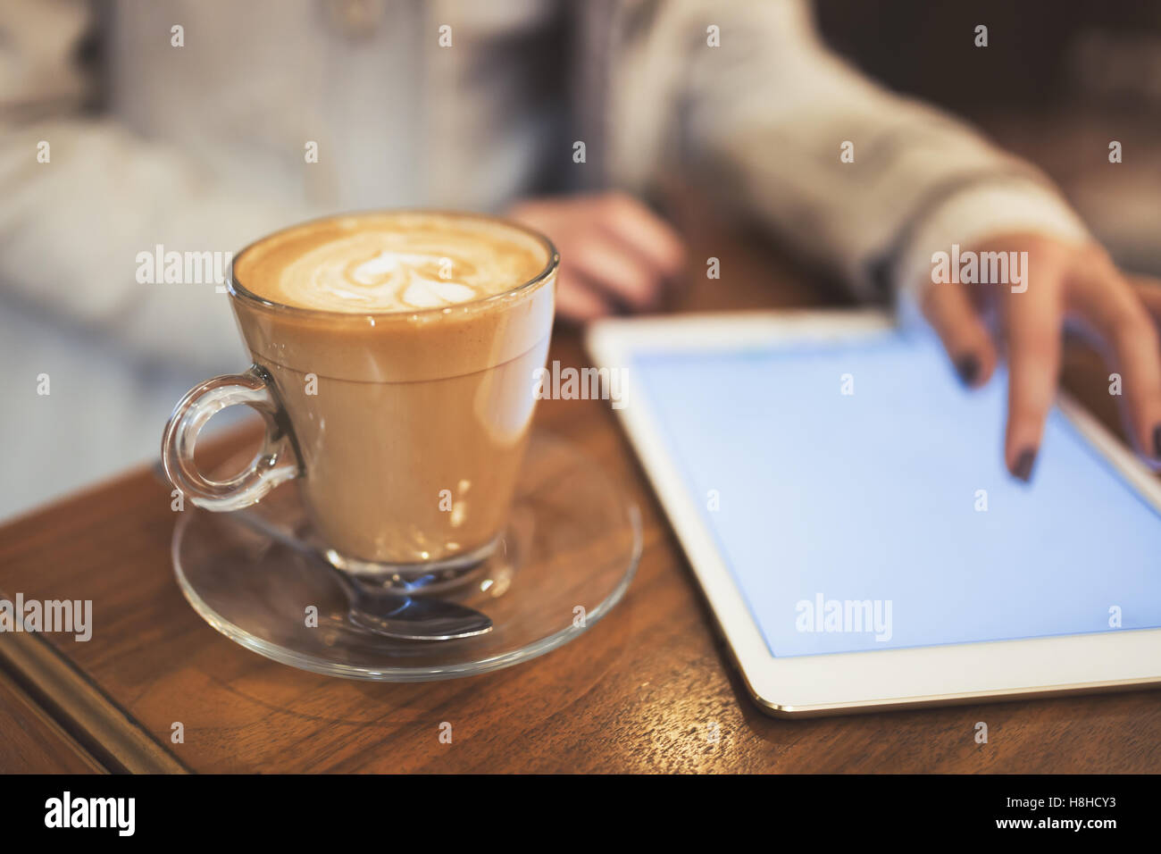 Woman using tablet in restaurant while on coffee break Stock Photo