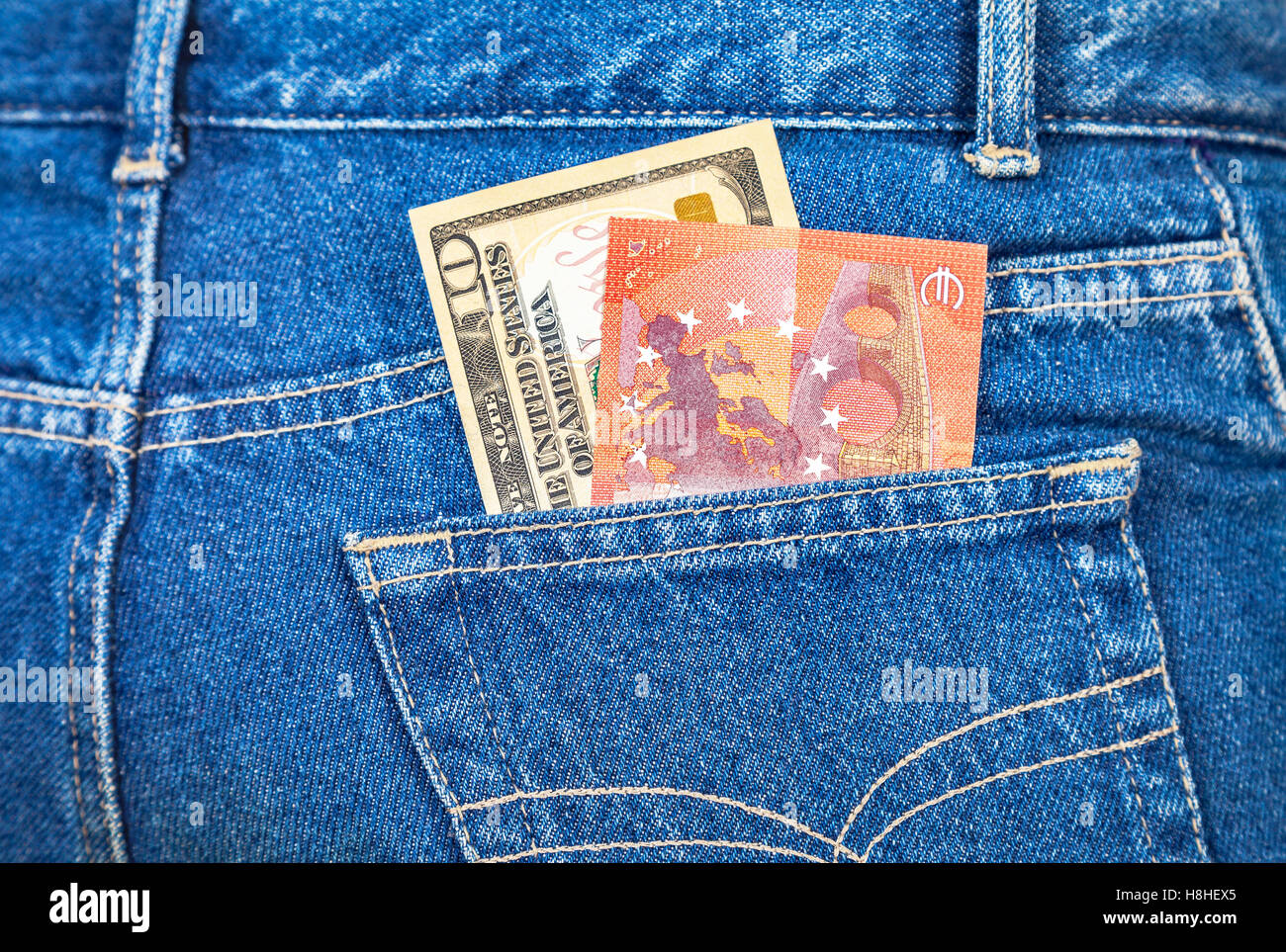 Ten american dollars and ten euro notes sticking out of the blue jeans pocket - Stock Image