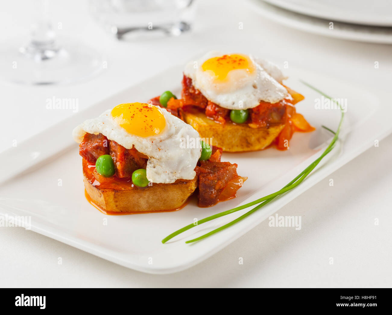 Chorizo and fried egg on a potato slice. Small tapa plate for sharing. - Stock Image