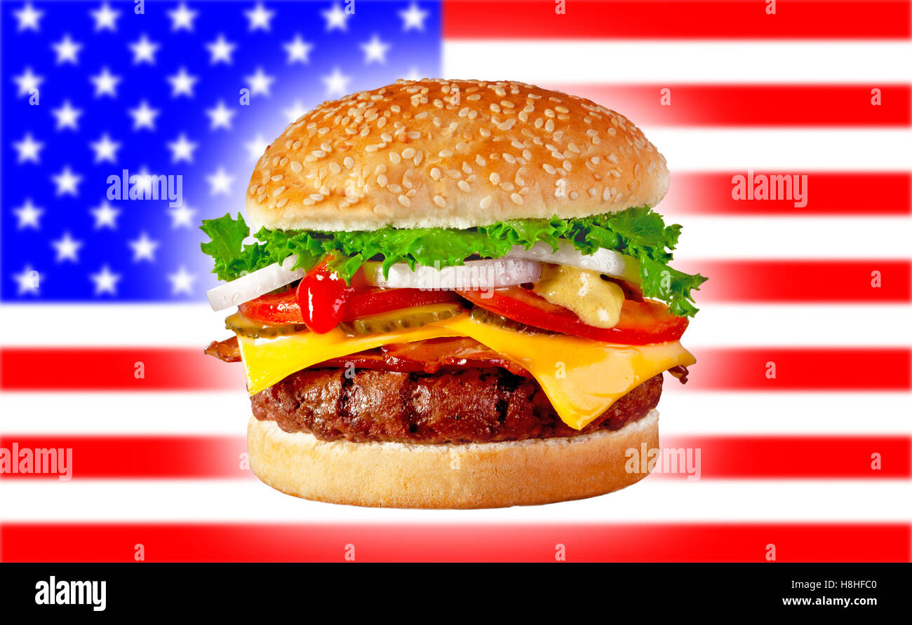 Juicy grilled hamburger with bacon and cheese on blurred USA flag background - Stock Image