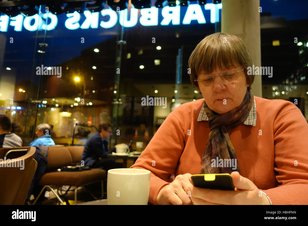 Woman using smartphone in cafe - Stock Image