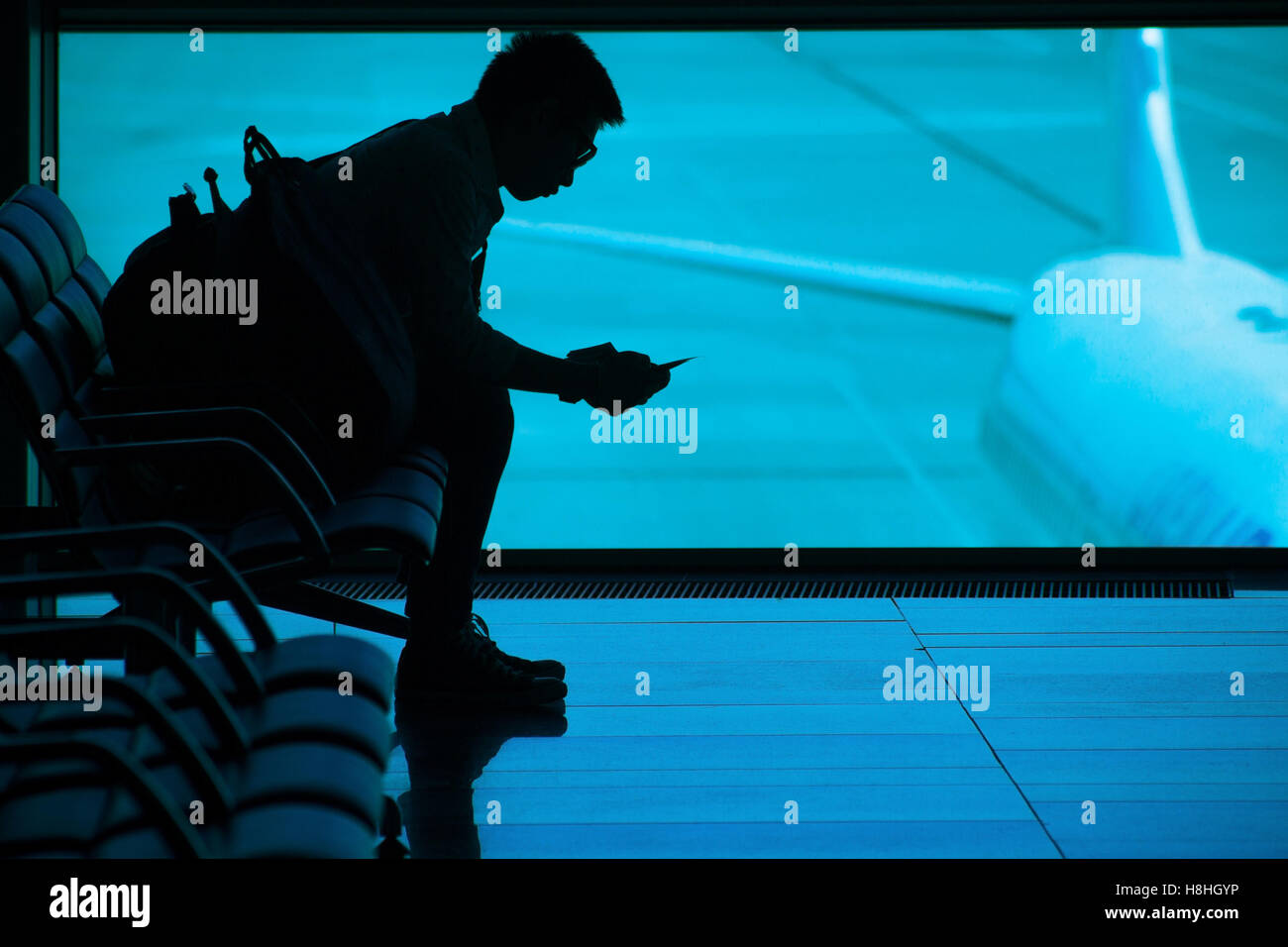 Passenger waiting at airport silhouette - Stock Image