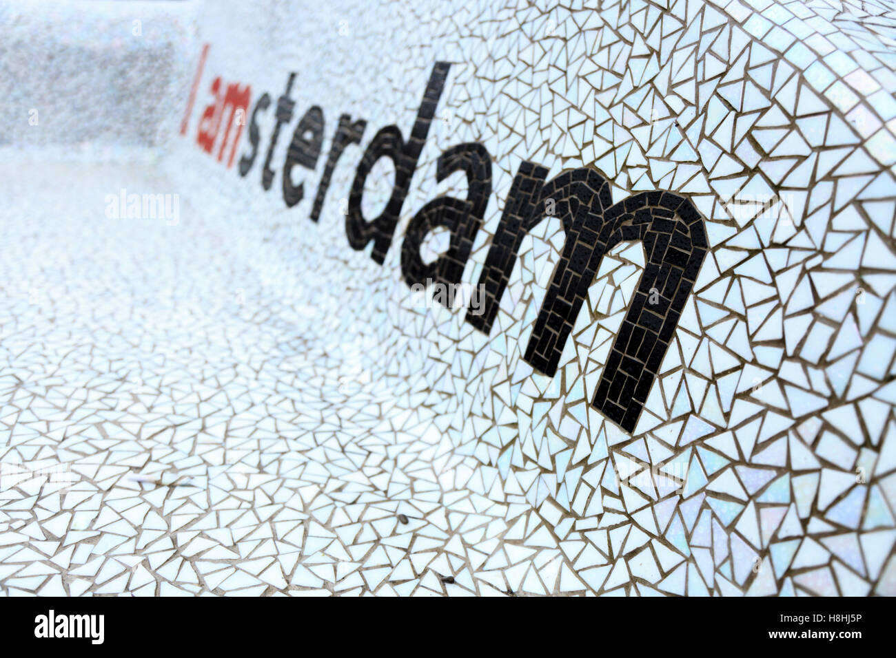 A tiled, mosaic, seat on the Museumplein in Amsterdam with the classic slogan Iamasterdam opicked out in black tiles. - Stock Image