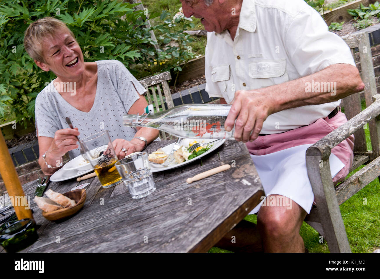 older folks enjoying lunch in pub garden using branded water red lion freehouse wiltshire - Stock Image