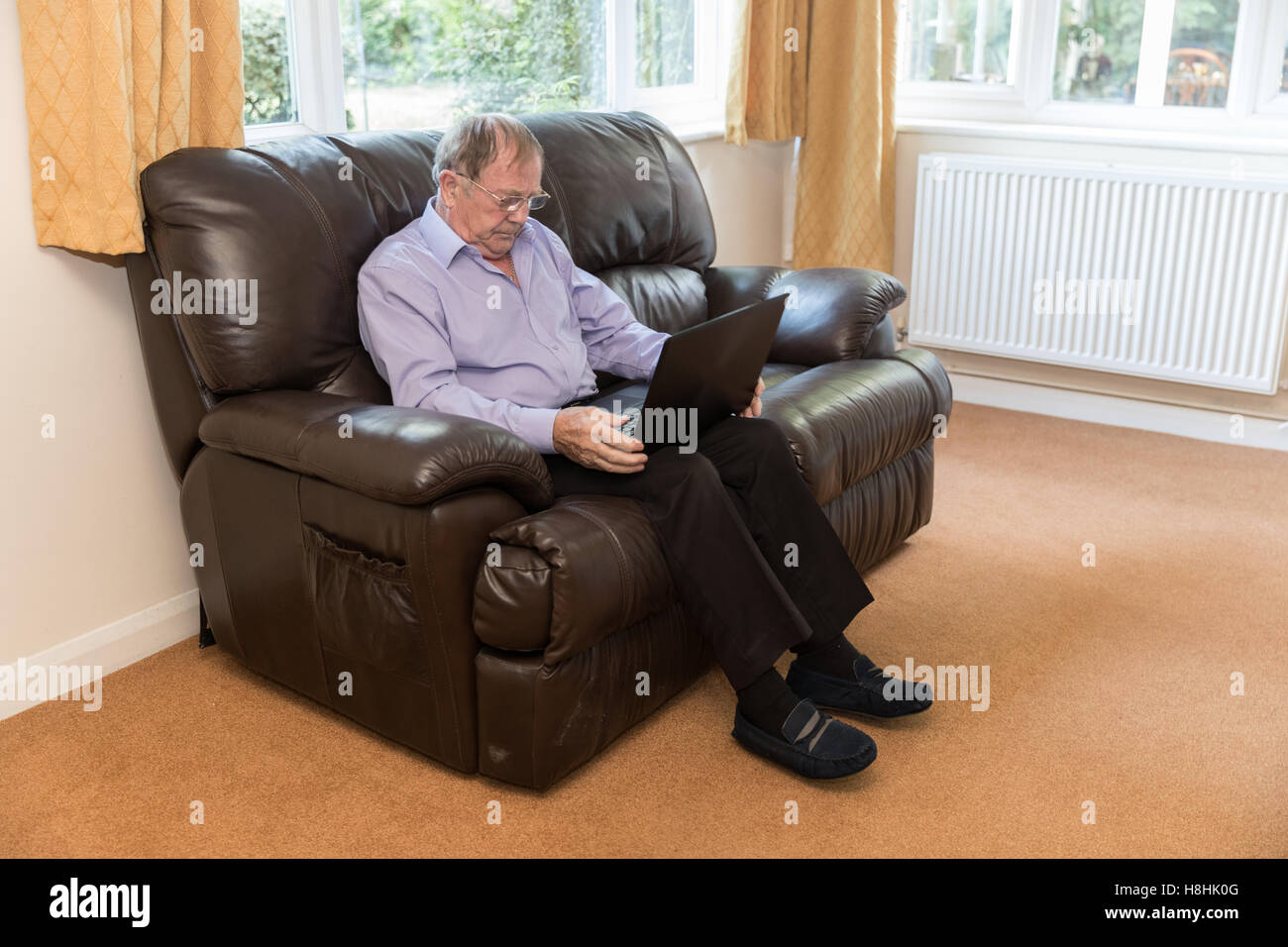 Old Man Sat On A Leather Sofa In His Lounge Wearing