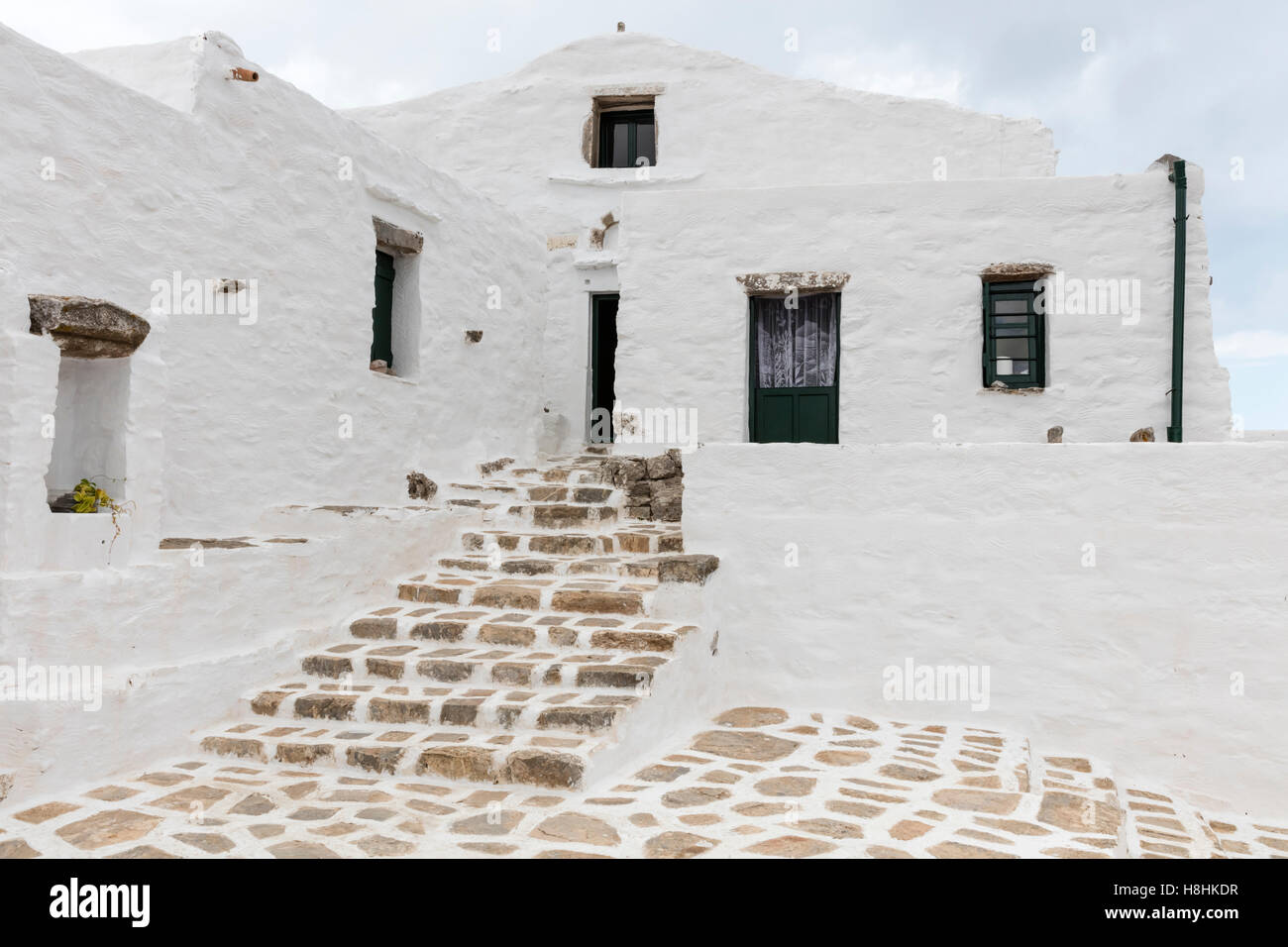 Courtyard and whitewashed stone buildings of the St John Theologia monastery on Amorgos in the Cyclades islands - Stock Image