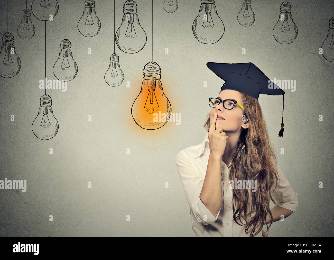 Closeup portrait beautiful thoughtful graduate student girl young woman in cap gown looking up at bright light bulb - Stock Image