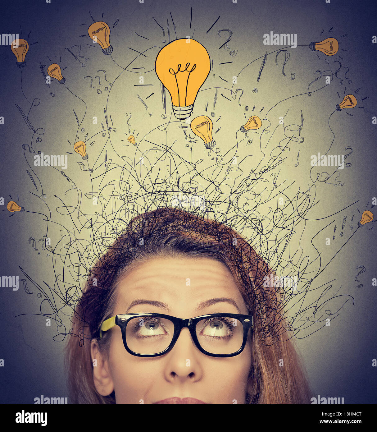 Closeup thinking woman with question signs and light idea bulb above head looking up on gray wall background - Stock Image