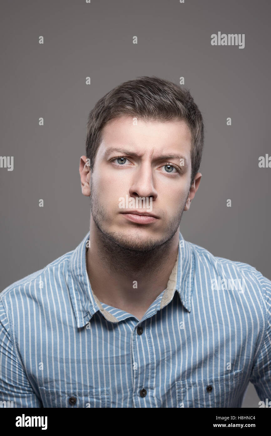 Moody portrait of distrustful young executive man in blue shirt looking at camera over gray background - Stock Image