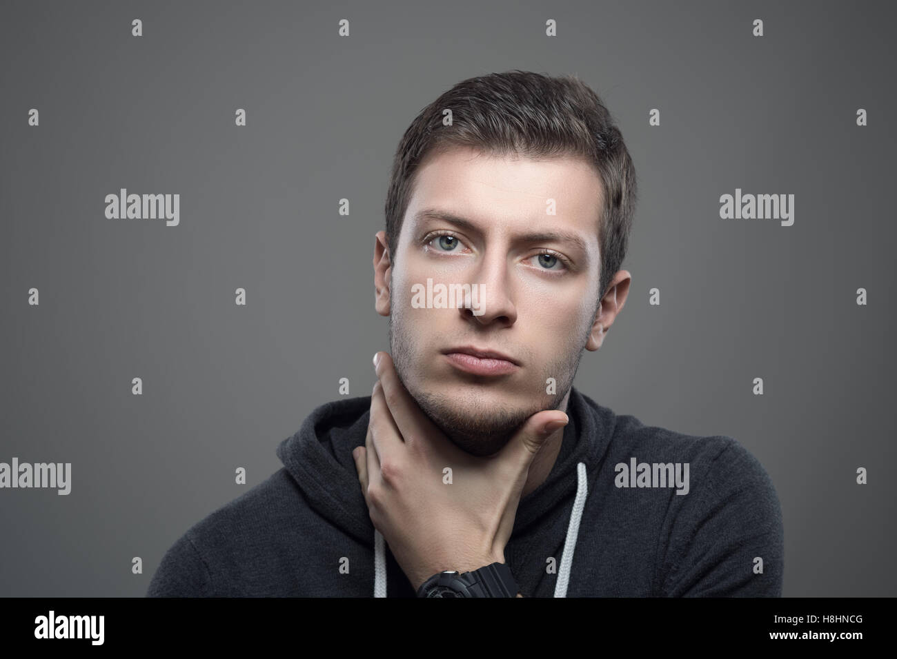 Moody portrait of serious young unshaven man with hand under chin looking at camera - Stock Image