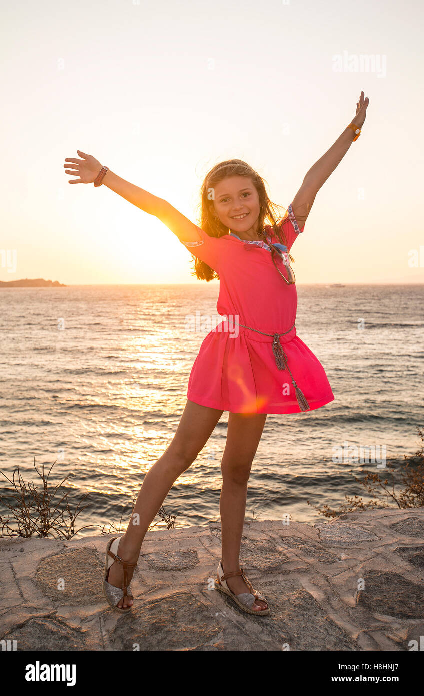 Happy young girl at Sunset - Stock Image