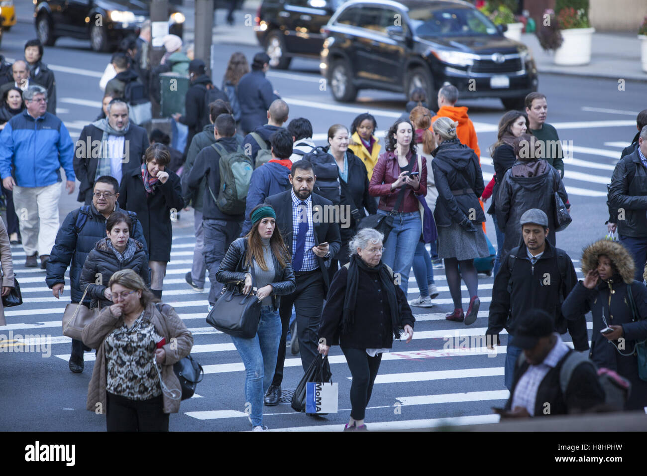 The crosswalks at 42nd Street and 5th Avenue are always clogged with pedestrians going here and there. NYC. - Stock Image