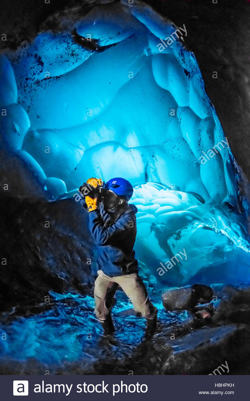 Photographer taking pictures inside an ice cave at Mendenhall Glacier, Juneau, Alaska USA. - Stock Image