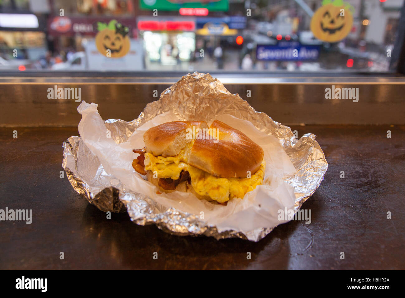 Bacon and egg toasted bagel at the Dali Market deli on 7th Avenue, Manhattan, New York City , United States of America. - Stock Image