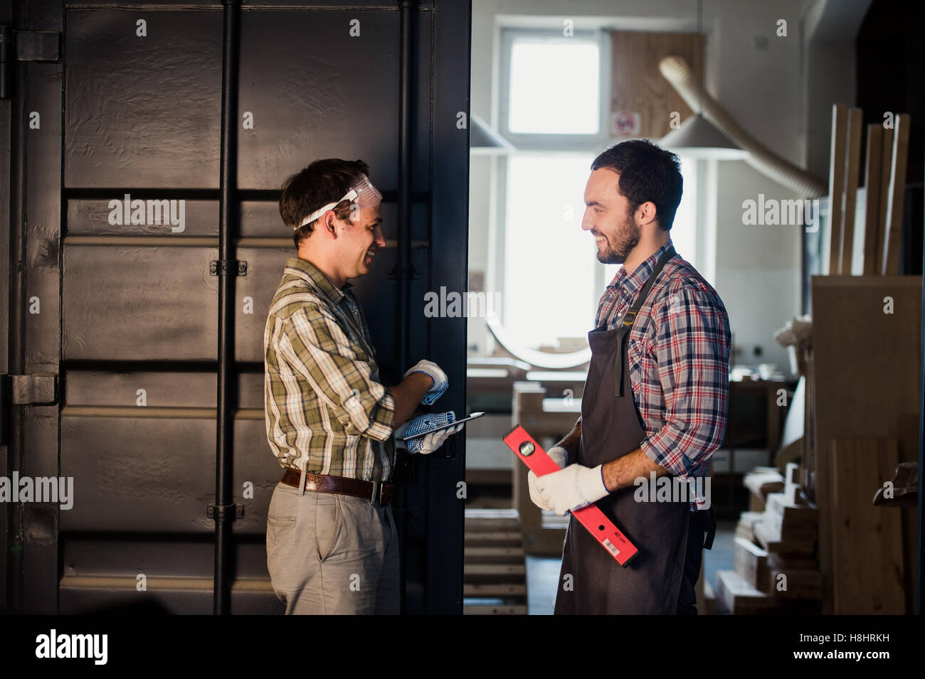 Male architects shaking hands at construction site - Stock Image