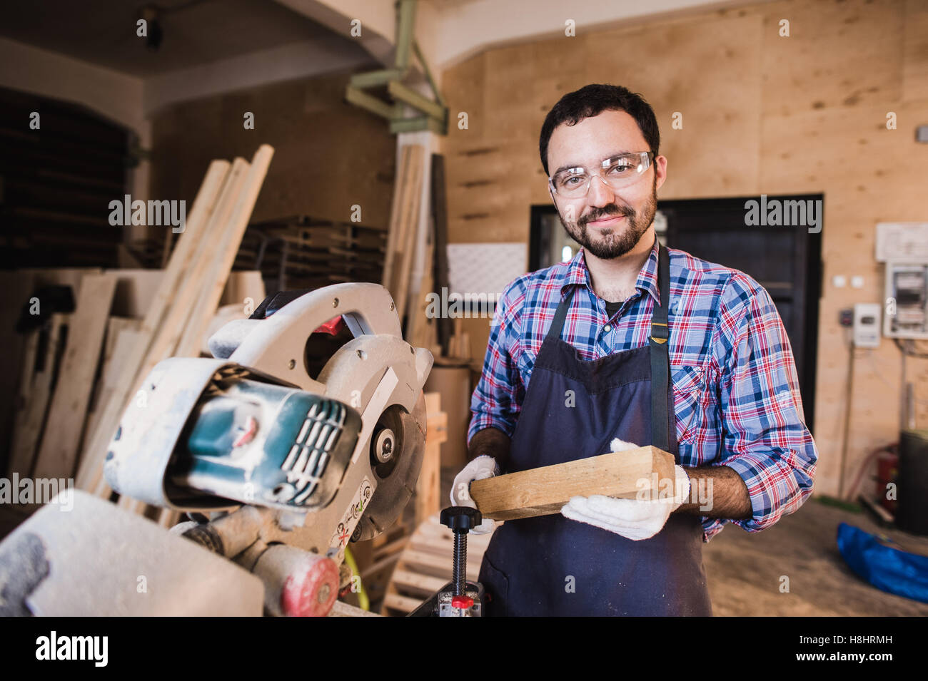 Young craftsman in uniform working at carpentry and looking to camera - Stock Image