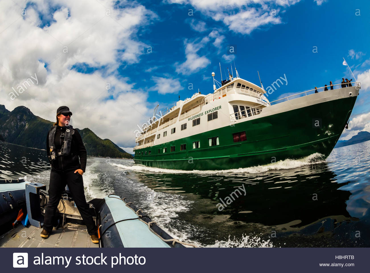 Skiff and Un-Cruise ship 'Wilderness Explorer', coming out of Takatz Bay, Baranof Island, Inside Passage, - Stock Image