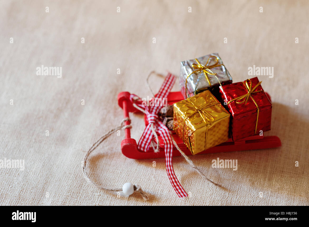 Christmas gift boxes on a red sleigh - tree decoration - Stock Image