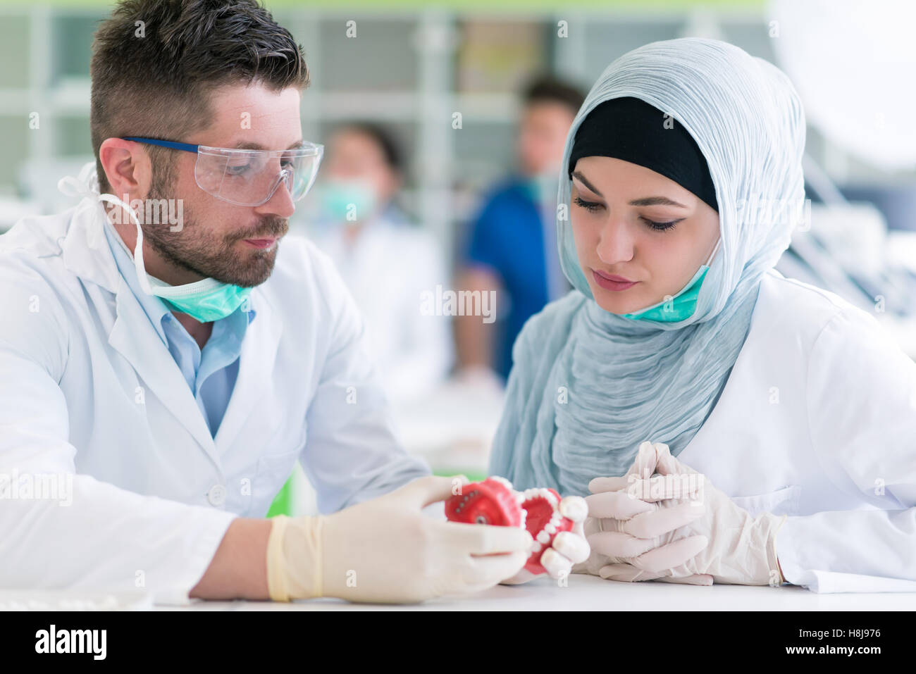 Arab students with hijab while working on the denture, false teeth. - Stock Image