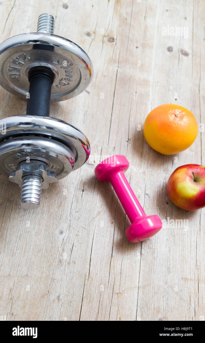 Weights and fruit on wooden background healthy living concept - Stock Image