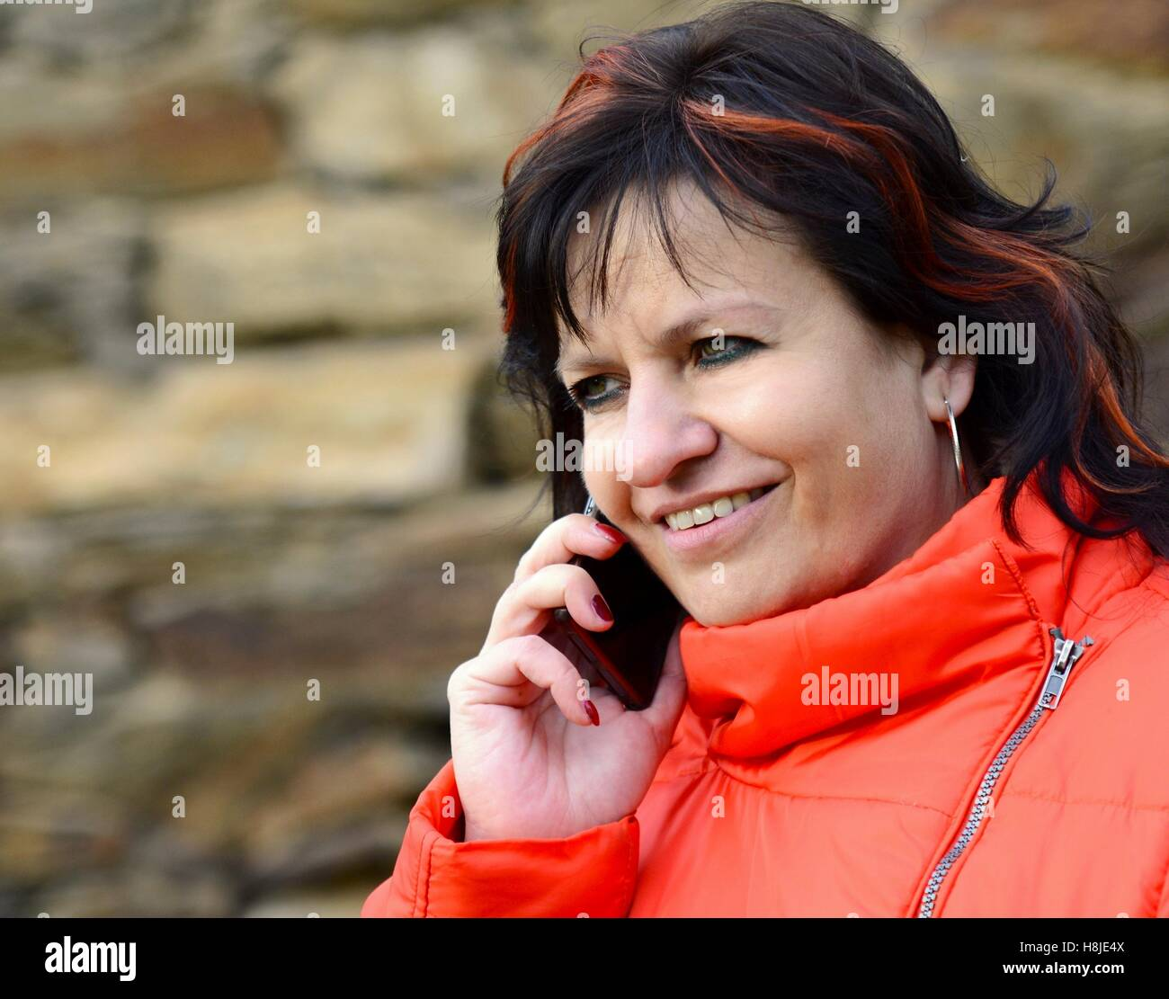 Middle aged ordinary caucasian woman standing in front of a stone wall with long dark hair and red jacket talking Stock Photo