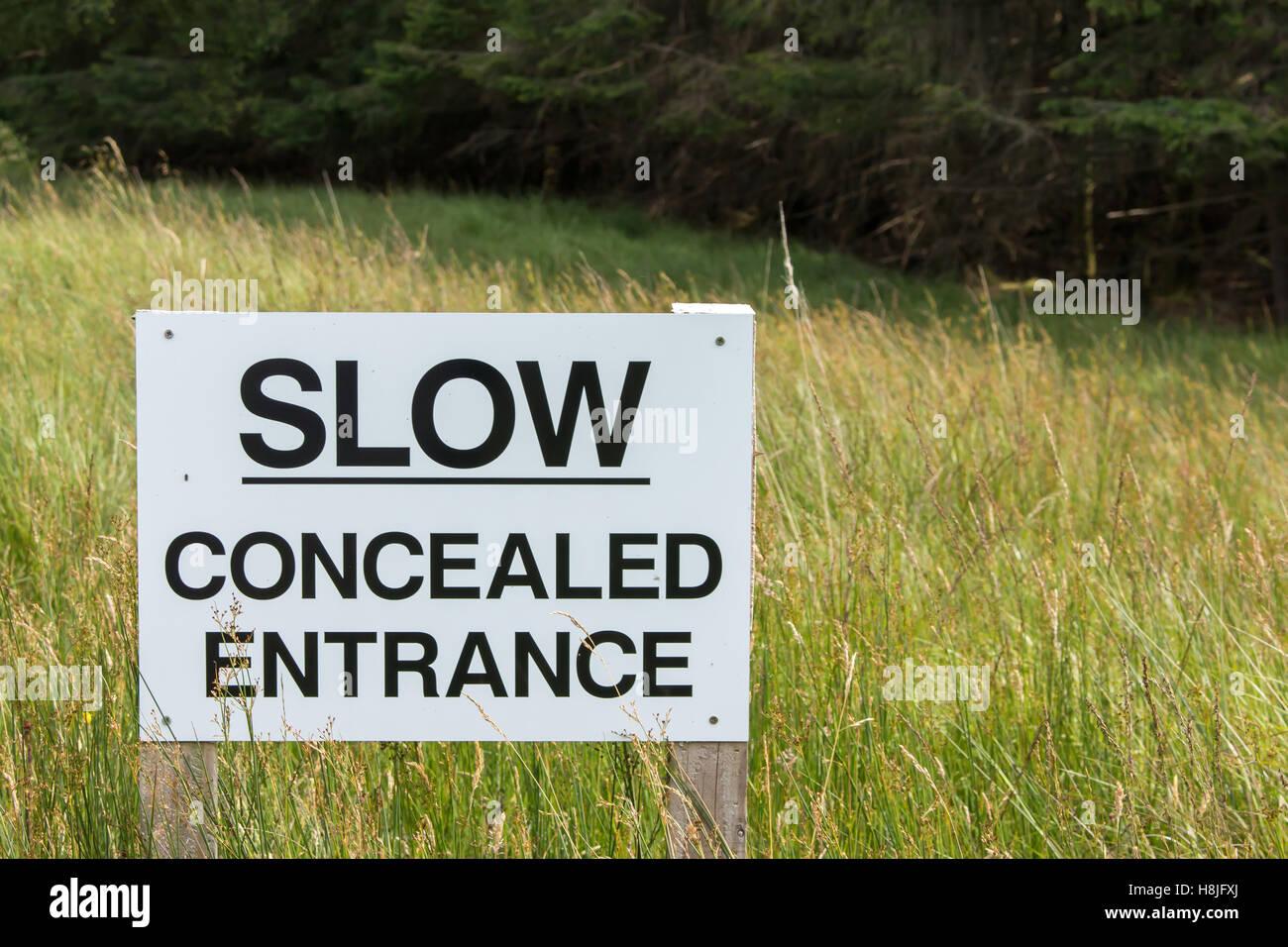 Sign warning, SLOW concealed entrance - Stock Image