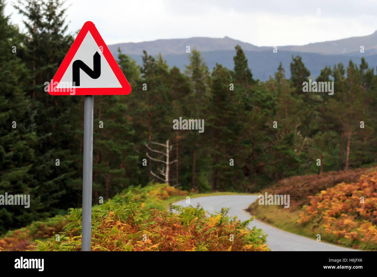 Triangular road sign warning of bends in the road - Stock Image