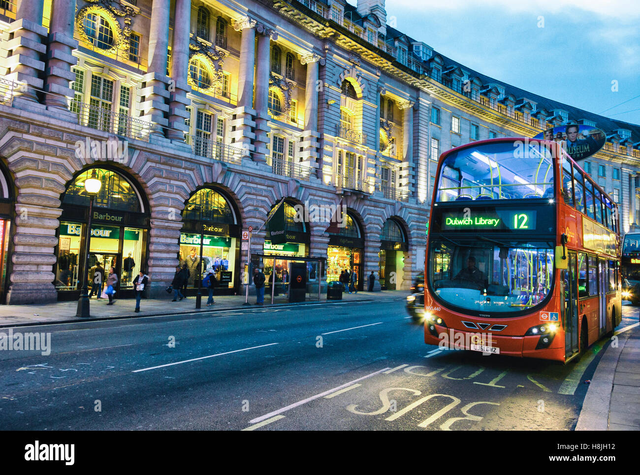 Traditional red bus in a street at dusk. - Stock Image