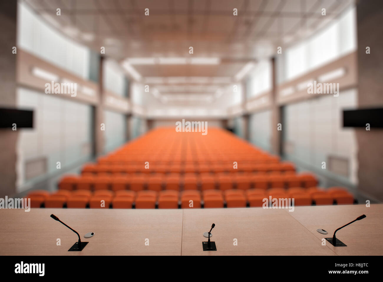 Abstract blur Rostrum with microphone and computer in conference hall. Orange color - Stock Image