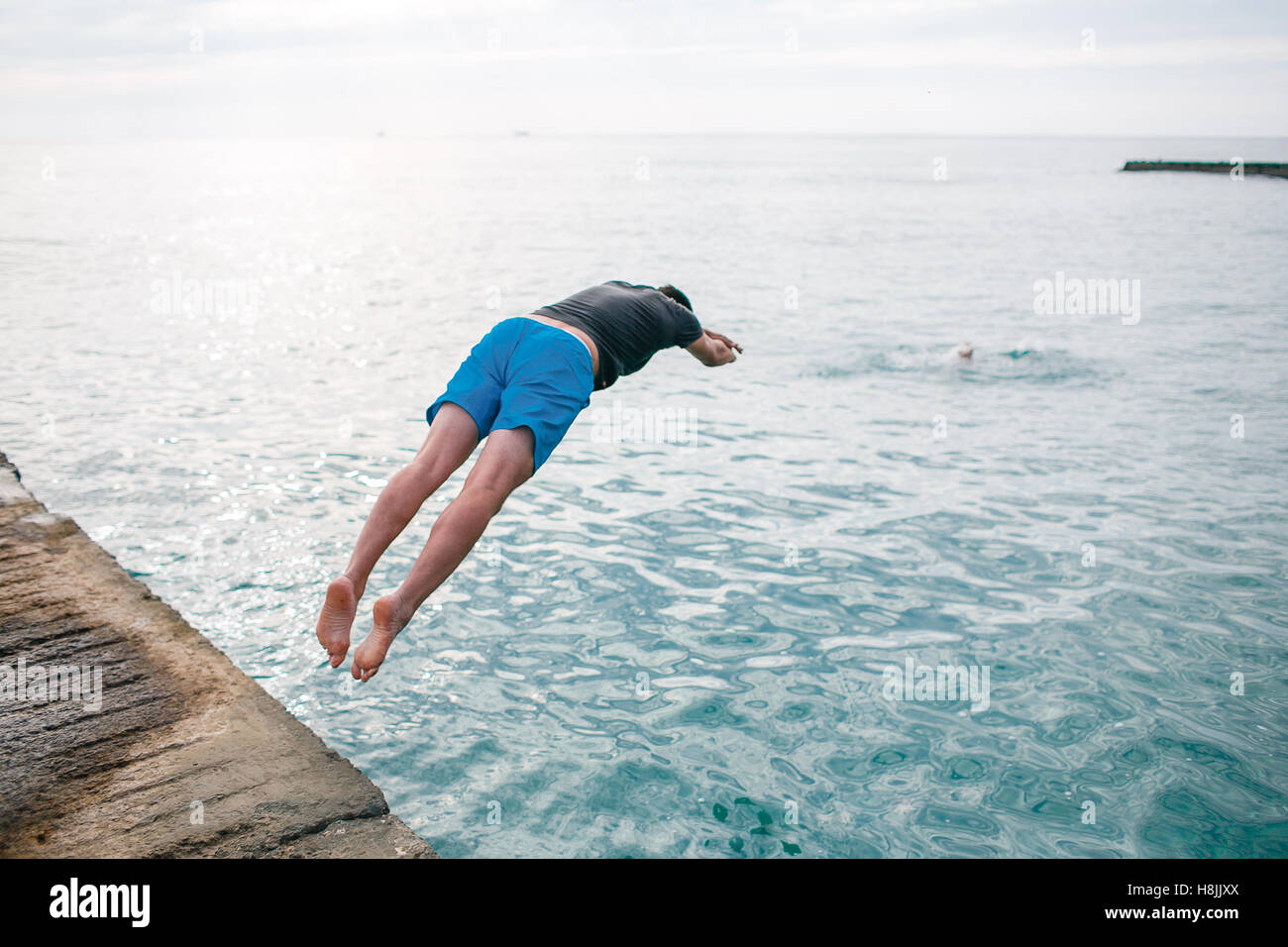 Young man jumping into water. save life.  drowns - Stock Image