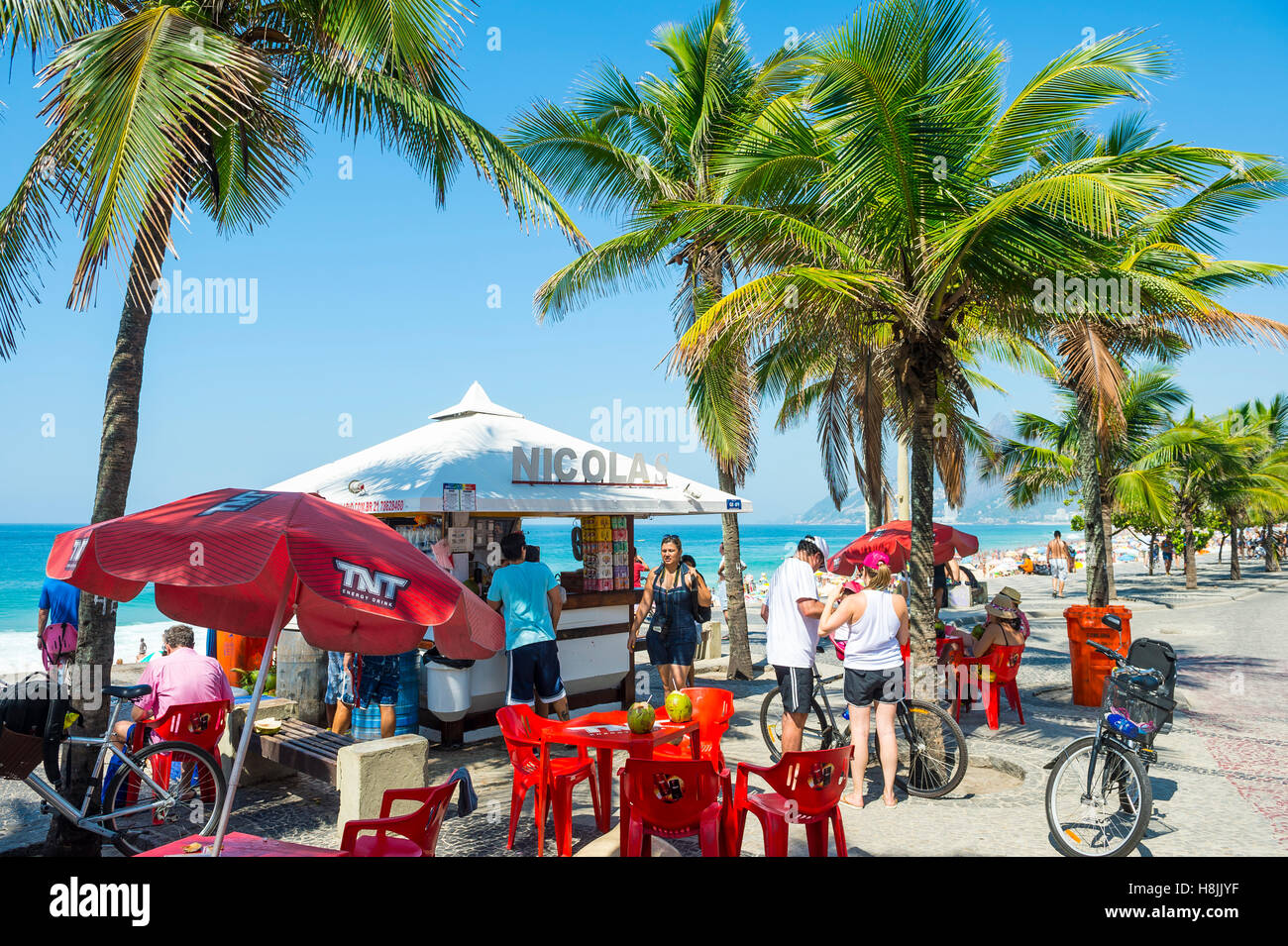 RIO DE JANEIRO - MARCH 20, 2015: Brazilians relax at a kiosk selling coconuts overlooking Ipanema Beach. - Stock Image