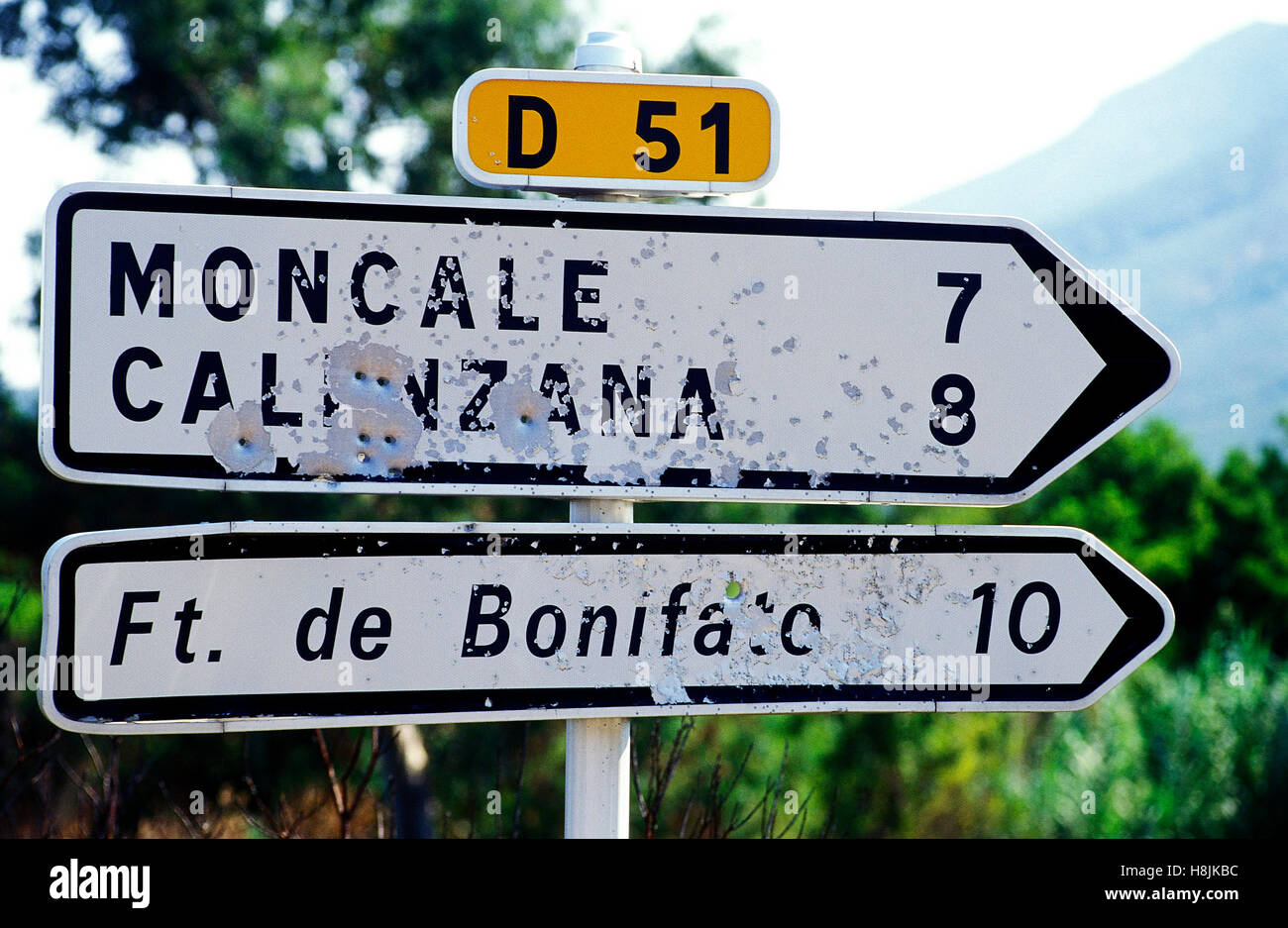 Road sign riddled with bullets in Corsica, France - Stock Image