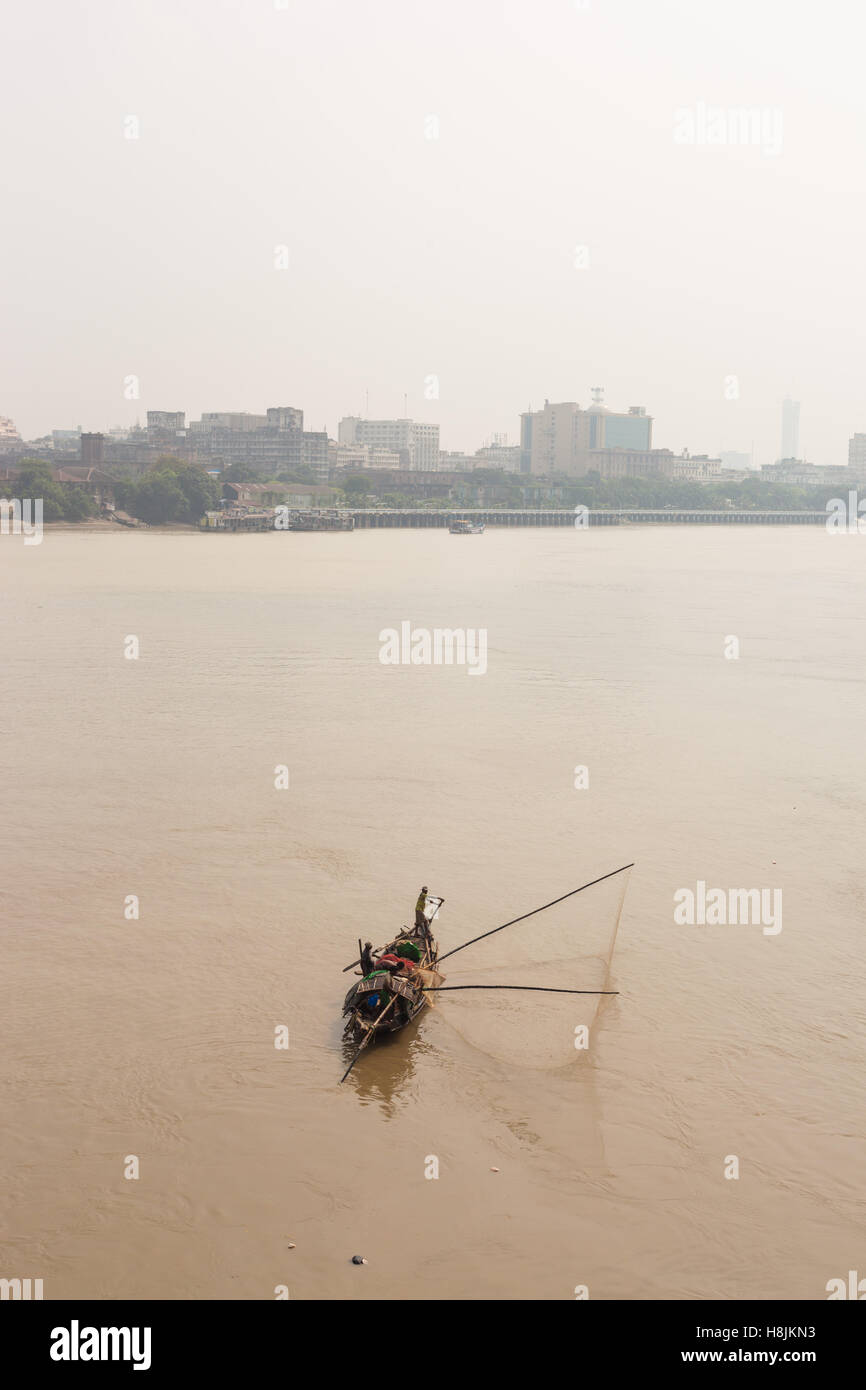 A traditional fishing boat deploys a net in the Hooghly River in Kolkata (Calcutta), West Bengal, India - Stock Image