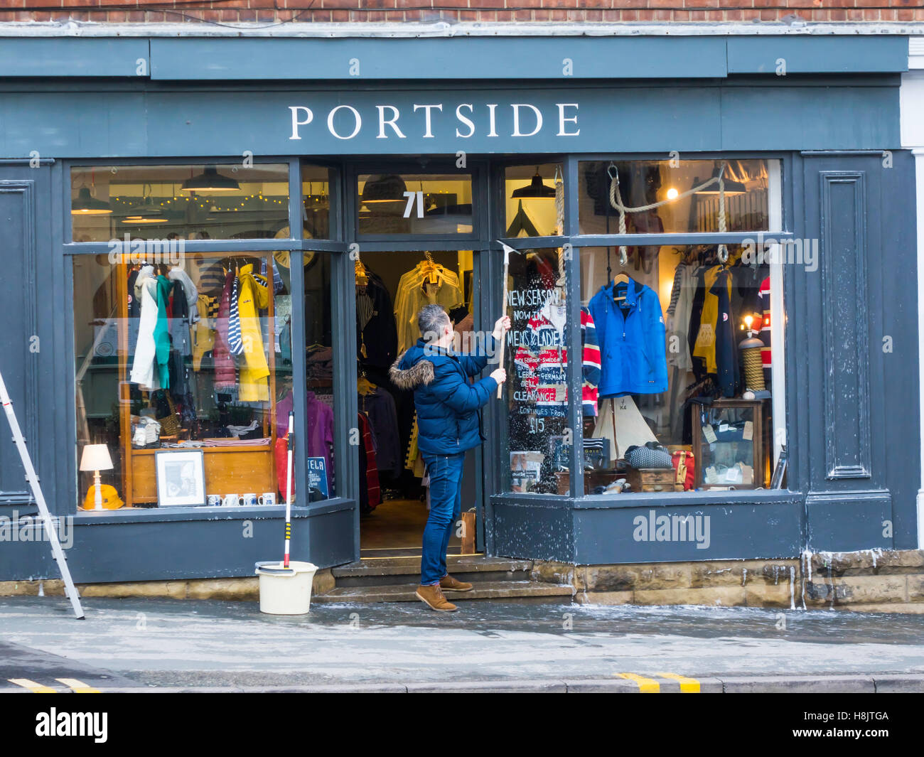 Man with mops and soapy water cleaning windows and paintwork on the front of 'Portside' a Clothing Shop - Stock Image